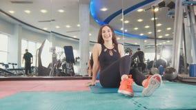 Unga kvinnor som övar sund livsstil i konditionstudio - straching i idrottshallen royaltyfri foto