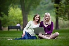 Unga kvinnor som använder bärbara datorn arkivbilder