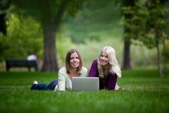 Unga kvinnor som använder bärbara datorn parkerar in fotografering för bildbyråer