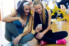 Unga kvinnor som använder mobiltelefonen i idrottshallen Fotografering för Bildbyråer