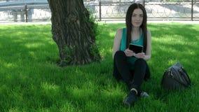 Unga kvinnor som arbetar på minnestavlaPC:N som sitter på korsat gräs, lägger benen på ryggen arkivfilmer