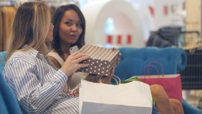 Unga kvinnor som avslutar blick in i shoppingpåsar i galleria Arkivbilder