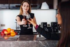 Unga kvinnor som bär den eleganta svarta klänningen som rymmer en flaska av rött vin och ett glass anseende på kökstången som ser Royaltyfri Fotografi