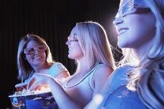 Unga kvinnor som bär exponeringsglas 3D i teater Fotografering för Bildbyråer