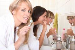 Unga kvinnor som borstar deras tänder Arkivfoton