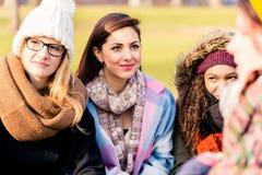 Unga kvinnor som dagdrömmer, medan dela idéer utomhus royaltyfri foto