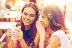 Unga kvinnor som dricker kaffe och talar på kafét Arkivbilder