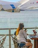 Unga kvinnor som dricker på strandstången royaltyfri bild