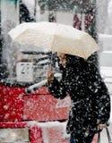 Unga kvinnor som en går under paraplyet i tungt snöfall i stadsgata arkivfoto