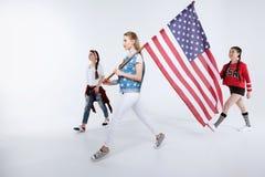 Unga kvinnor som går med amerikanska flaggan och firar 4th juli Royaltyfria Foton