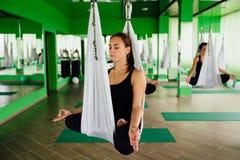 Unga kvinnor som gör antigravity yoga, övar med en grupp människor aero klipsk konditioninstruktörgenomkörare vita hängmattor Royaltyfria Bilder