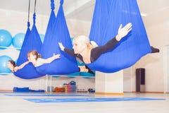 Unga kvinnor som gör flyg- yogaövning eller antigravity yoga Royaltyfri Foto