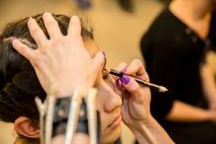 Unga kvinnor som gör makeup som är gammalmodig backstabbing fotografering för bildbyråer