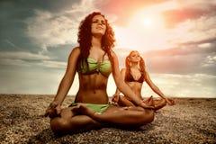 Unga kvinnor som gör yoga på stranden Royaltyfria Foton