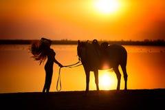 Unga kvinnor som går med hennes häst Arkivbild