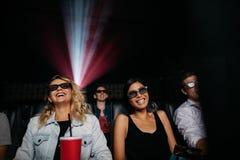 Unga kvinnor som håller ögonen på filmen 3d i teater Arkivbild
