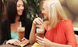 Unga kvinnor som har kaffeavbrottet tillsammans arkivbild
