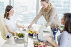 Unga kvinnor som har matställen tillsammans i modernt kök Arkivbilder