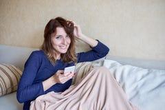 Unga kvinnor som hemma använder hennes smarta telefon på soffan i vardagsrummet royaltyfri foto