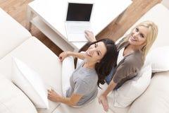Unga kvinnor som hemma använder bärbar datordatoren på sofaen Royaltyfri Fotografi