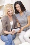Unga kvinnor som hemma använder Tabletdatoren Arkivbilder