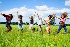 Unga kvinnor som hoppar med glädje Fotografering för Bildbyråer