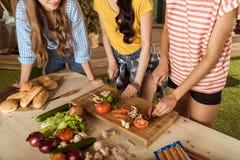 Unga kvinnor som klipper nya grönsaker på trätabellen Royaltyfri Fotografi