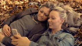 Unga kvinnor som kopplar av med vännen på, parkerar arkivfilmer