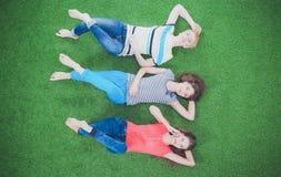 Unga kvinnor som ligger på grönt gräs Unga kvinnor Arkivfoton