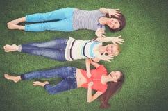 Unga kvinnor som ligger på grönt gräs Unga kvinnor Royaltyfria Bilder