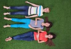 Unga kvinnor som ligger på grönt gräs Unga kvinnor Royaltyfria Foton