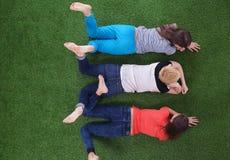 Unga kvinnor som ligger på grönt gräs Unga kvinnor Fotografering för Bildbyråer