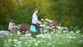 Unga kvinnor som rider på hästar till och med ängen på solnedgången arkivfilmer