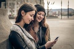 Unga kvinnor som ser en mobiltelefon Fotografering för Bildbyråer