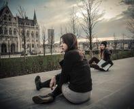 Unga kvinnor som sitter i en trädgård Arkivbilder