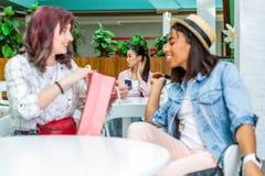 Unga kvinnor som sitter med den shoppingpåsen och flickan som använder smartphonen bakom i shoppinggallerian, unga flickor som sh Royaltyfria Bilder