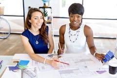Unga kvinnor som sitter på ett skrivbord i ett kontor och ett arbete på ritning Fotografering för Bildbyråer