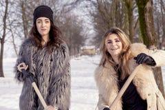 Unga kvinnor som skyfflar snö nära ett litet trä Royaltyfria Foton