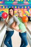 Unga kvinnor som spelar bowling och har gyckel Arkivfoto