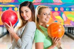 Unga kvinnor som spelar bowling och har gyckel Arkivbild