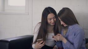 Unga kvinnor som talar att rymma, ringer i händer inomhus De ser med intresse på skärmen av den silvriga smartphonen arkivfilmer