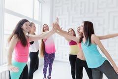 Unga kvinnor som tillsammans bär sammanfogande händer för sportswear arkivbild