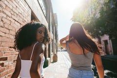 Unga kvinnor som tillsammans går på trottoaren Royaltyfria Bilder