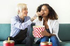 Unga kvinnor som tillsammans håller ögonen på en film arkivbild