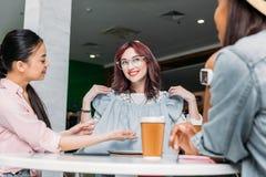 Unga kvinnor som tillsammans sitter i shoppinggalleria med nya trendiga kläder, unga flickor som shoppar begrepp Arkivbilder