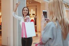 Unga kvinnor som tycker om att shoppa tillsammans på gallerian fotografering för bildbyråer