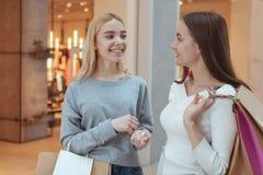 Unga kvinnor som tycker om att shoppa tillsammans på gallerian arkivfoton