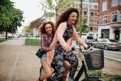 Unga kvinnor som tycker om cykeln, rider på stadsgatan Royaltyfria Bilder