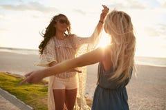 Unga kvinnor som tycker om en dag på stranden och har gyckel arkivbilder