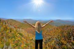 Unga kvinnor som tycker om solen och härligt nedgånglandskap Royaltyfri Foto